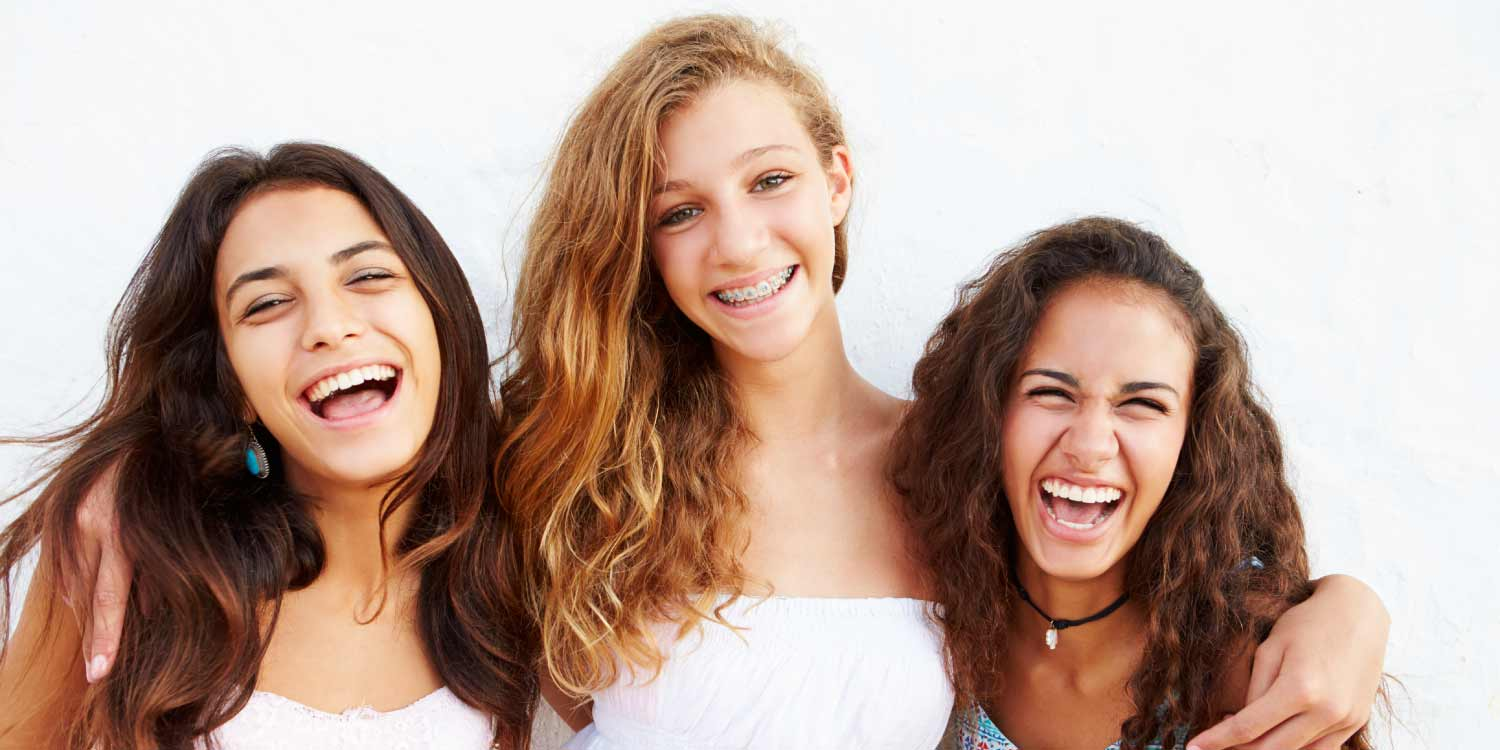 3 teenage girls smile, two without braces and one with braces who keeps her mouth clean