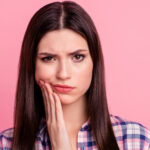 Brunette woman in a plaid shirt cringes and frowns because of her braces pain