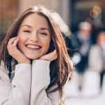 Brunette woman with clear braces smiles happily in Weatherford, TX