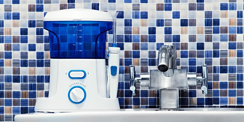 Closeup of a water flosser on a white sink against a blue mosaic backsplash