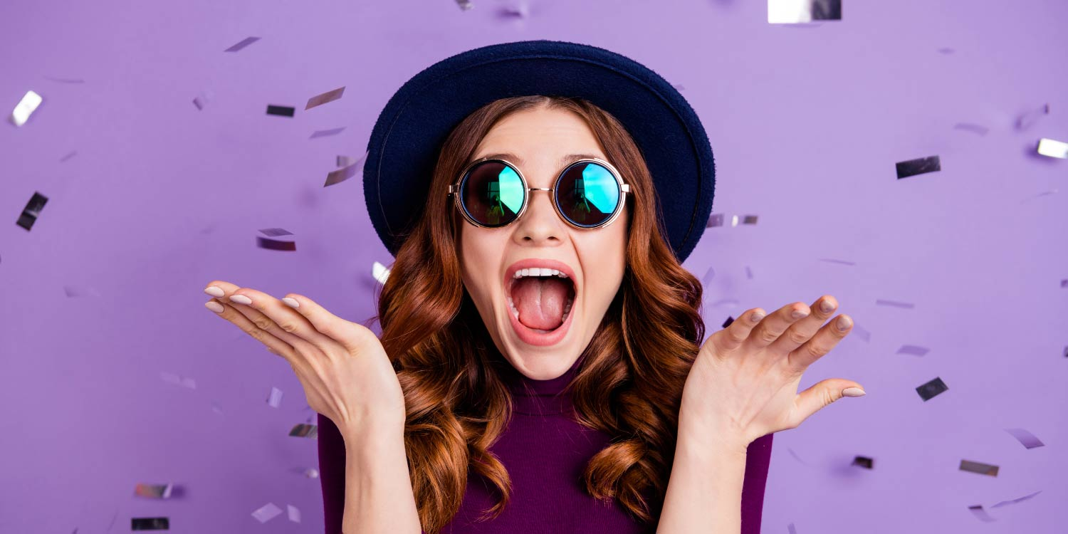 Brunette woman in a black hat and sunglasses celebrates with purple confetti getting her braces off