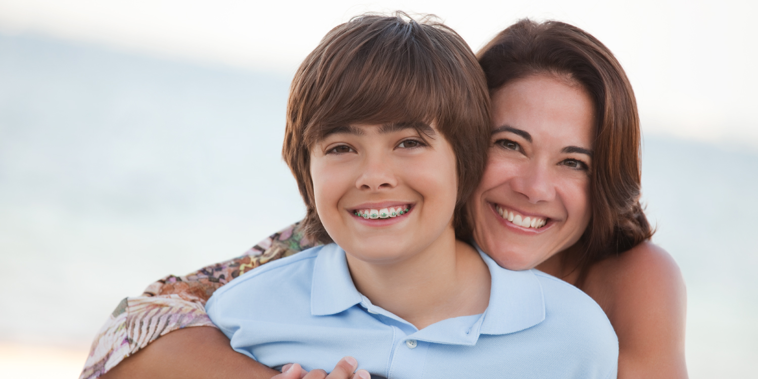Brunette boy with braces smiles on the beach with his brunette mother