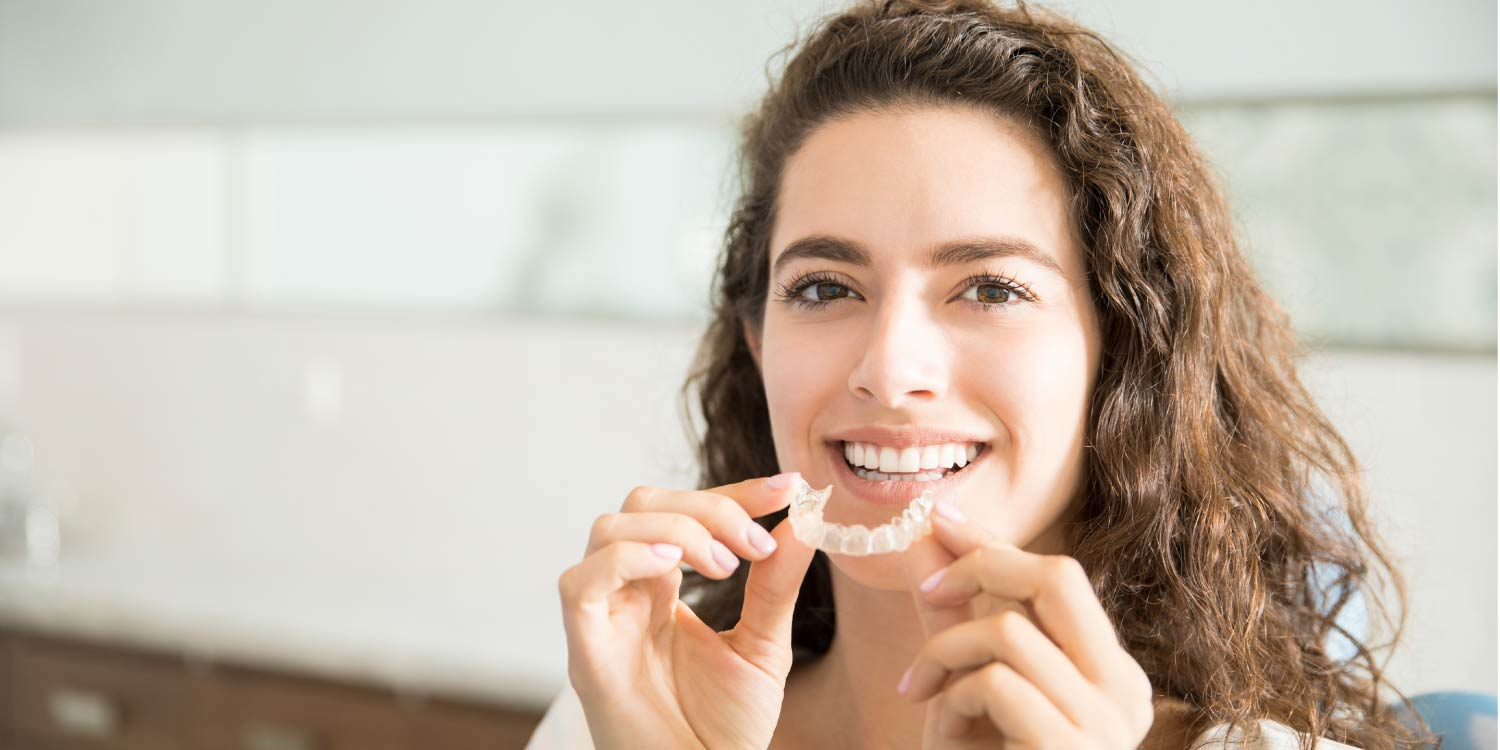 brunette woman smiles as she puts in her Invisalign clear aligners to fix her crooked teeth