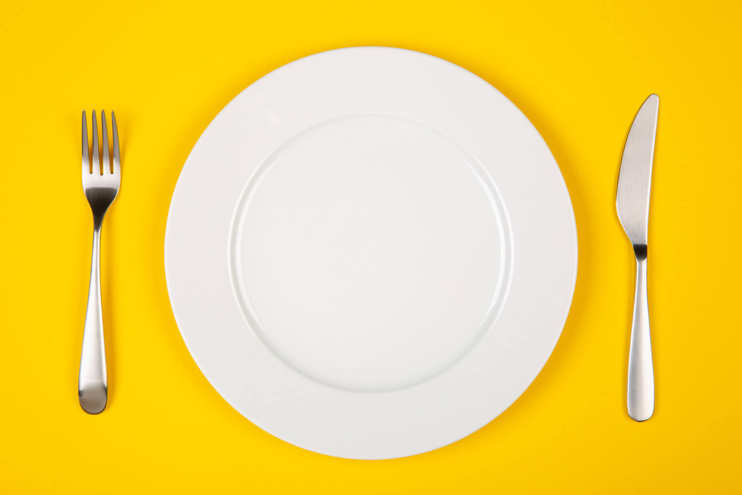 Aerial view of an empty place setting on a yellow background