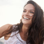 Brunette woman with straight teeth smiles after getting her braces off because of all the benefits of straight teeth