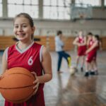 Young girl in a red jersey holds a basketball while wearing braces inside on a basketball court